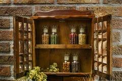 Gabinete de madera del estante o de almacenamiento de especia del vintage y seis bottl del vidrio imagen de archivo