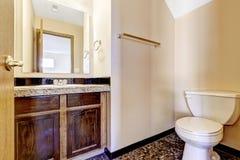 Gabinete de madera viejo de la vanidad del cuarto de baño con el top del granito Fotografía de archivo