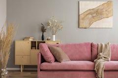 Gabinete de madera y pintura abstracta detrás del sofá rosado en interior elegante de la sala de estar fotos de archivo