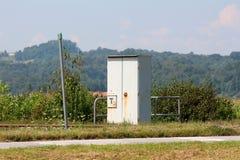 Gabinete gris del metal del ferrocarril al aire libre protegido con la cerca fuerte del metal al lado de pistas de ferrocarril fotos de archivo