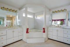 Gabinetes de cuarto de baño principales blancos grandes de lujo con los fregaderos dobles y la tina de baño grande Imagenes de archivo