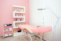 Gabinetto del cosmetologo con la tavola di massaggio nel salone moderno di bellezza Interno medico del gabinetto immagine stock libera da diritti