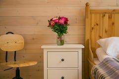 Gabinetto di legno bianco con il vaso ed i fiori rosa fotografia stock libera da diritti