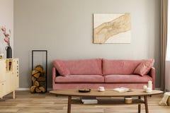 Gabinetto e ceppo di legno di legno accanto allo strato rosa nell'interno elegante del salone immagine stock
