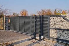 Free Gabion. Automatic Entrance Gate Used In Combination With A Wall Made Of Gabion Stock Photo - 164251100