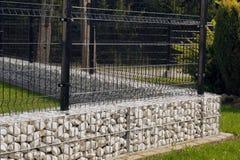 Gabion Ett lågt fundament under ett openwork staket för stål arkivbilder