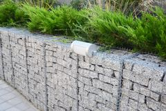 Gabion fence with stones in wire mesh and outdoor lighting. Gabion wire mesh fencing with natural stones royalty free stock images