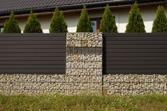Gabion. The house is surrounded by a fence made of, among others Royalty Free Stock Photos