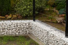 Gabion. A steel fence combined with a low wall made of gabions f Stock Image