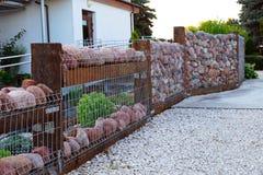 Gabion Una casa con una cerca hecha de piedras del guijarro fotos de archivo