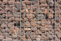Gabion vägg som fylls med lavastenar Arkivfoton