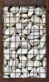 Gabion with white pebbles. Garbione with white stones and rusted grid stock image