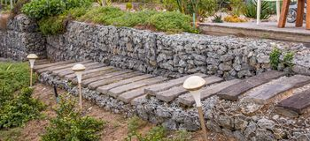 Gabion is a wire cage filled with rocks for civil engineering applications. Gabion is a wire cage filled with rocks for use in civil engineering, road building stock image