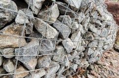 Gabiondozen die een rivier beschermen tegen erosie Stock Foto