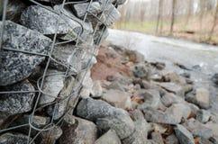 Gabiondozen die een rivier beschermen tegen erosie Stock Afbeeldingen