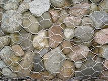 A steel mesh filled with stones stock photography