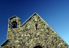 Gable end of stone church. Roof with bell tower, blue sky background stock images