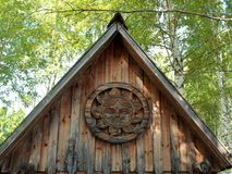 Gable old wooden house on the background of birches and blue sky. On the pediment round emblem of the sun in Russian village stock images