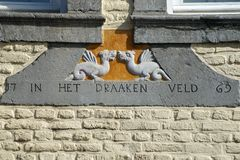 Gable ornament with text. `In the dragon field` in the facade of an historic building in Maasstricht, The Netherlands stock image