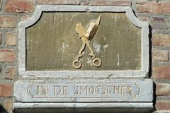Gable ornament with text. `In the scissors` in the facade of an historic building in Maasstricht, The Netherlands stock photos