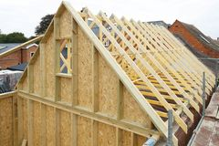 Timber frame house roof. Gable and wooden roof trusses to a timber frame house under construction royalty free stock photo