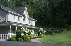 Gabled house. Grey stone house with white porch Stock Photos