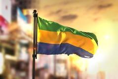 Gabon Flag Against City Blurred Background At Sunrise Backlight. Sky Royalty Free Stock Photos