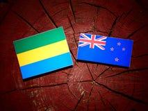 Gabon flag with New Zealand flag on a tree stump isolated. Gabon flag with New Zealand flag on a tree stump royalty free illustration