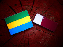 Gabon flag with Qatari flag on a tree stump isolated Royalty Free Stock Image