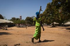 Irl wearing a colorful dress at the village of Mandina Mandinga in the Gabu Region with a mosque on the background. Gabu Region, Republic of Guinea-Bissau stock images