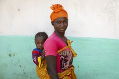 Portrait of of a woman carrying her baby daughter on her shoulders, in the village of Mandina Mandinga in the Gabu Region. Gabu Region, Republic of Guinea-Bissau stock photos