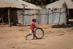 Young boy playing with an old tire, in the village of Mandina Mandinga in the Gabu Region. Gabu Region, Republic of Guinea-Bissau - February 7, 2018: Young boy stock photo