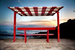 Gacebo på stranden på solnedgången med bergbakgrunden royaltyfri bild