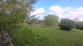 Gacelas hermosas que caminan en el prado verde, el Skyride y la vista parcial del roller coaster de la caza del guepardo almacen de metraje de vídeo