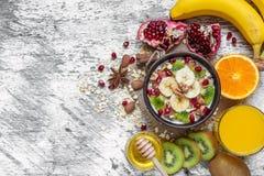 Gachas de avena de la harina de avena con el plátano, la fruta de kiwi, la granada, el canela y nueces Fotos de archivo libres de regalías