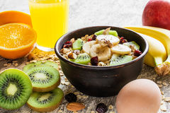 Gachas de avena de la harina de avena en un cuenco con las frutas, las nueces, el huevo y el zumo de naranja fresco Fotografía de archivo libre de regalías