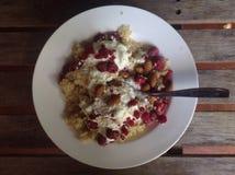 Gachas de avena de la quinoa con las frambuesas, las almendras y el yogur Imagen de archivo libre de regalías
