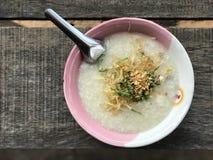 Gachas de avena del arroz con el cerdo asperjado con el jengibre cortado y el ajo frito Foto de archivo libre de regalías