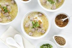 Gachas de avena del arroz con las chuletas de cerdo y condimento en los cuencos blancos en la tabla blanca de la visión superior, fotos de archivo