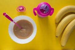 Gachas de avena del bebé para el bebé y plátanos en plátanos de un fondo del amarillo fotografía de archivo