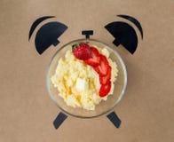 Gachas de avena del maíz con las fresas en la forma del despertador, concepto del tiempo de desayuno Imagen de archivo libre de regalías