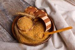Gachas de avena del trigo en un cuenco de madera en una tabla con un paño fotografía de archivo libre de regalías