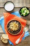 Gachas de avena hechas con arroz salvaje y lentejas negras con las cebollas fritas Imagen de archivo