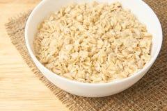 Gachas de avena de la harina de avena Tazón de fuente blanco Fondo ligero Alimento sano Foto de archivo