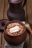 Gachas de avena recientemente cocinadas del alforfón en un pote de arcilla Imagenes de archivo