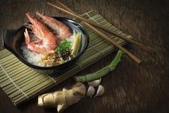 Gachas del arroz mezcladas con la gamba y el jengibre, rebanada de la cebolleta y pimienta frita del ajo y negra en cuenco negro  fotos de archivo