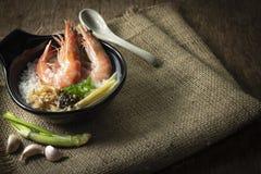 Gachas del arroz mezcladas con la gamba y el jengibre, rebanada de la cebolleta y pimienta frita del ajo y negra en cuenco negro  imagen de archivo libre de regalías