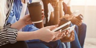 Gadżetu i kawy nałóg Nastolatkowie używa telefony obraz royalty free