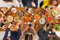 Gadżetu przyrządu nałóg, przyjaciele obiadowi z smarphones obraz royalty free