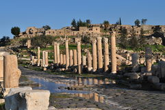 Gadara Main Road. Umm Qais road and Roman Pillars reflection on water Royalty Free Stock Photo